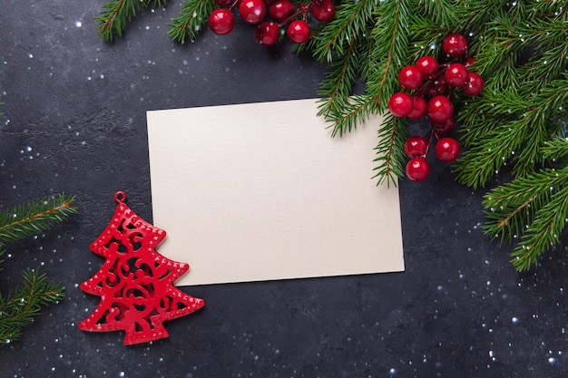 Christmas card with paper and fir tree branch on black background Premium Photo