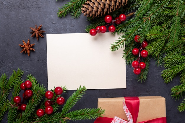 Christmas card with paper, gift box and fir tree branch on black background Premium Photo