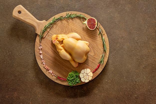 Рождественская курица перед приготовлением. кукурузная курица на круглой разделочной деревянной доске готова к приготовлению с розовой гималайской солью, розмариновым чесноком, острым перцем и инжиром. крупный план. вид сверху. copyspace. Premium Фотографии
