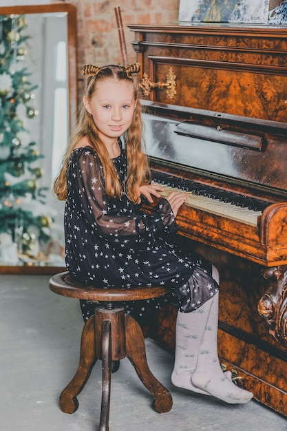 Christmas child little girl playing on piano at home. a girl plays the piano at christmas. Premium Photo
