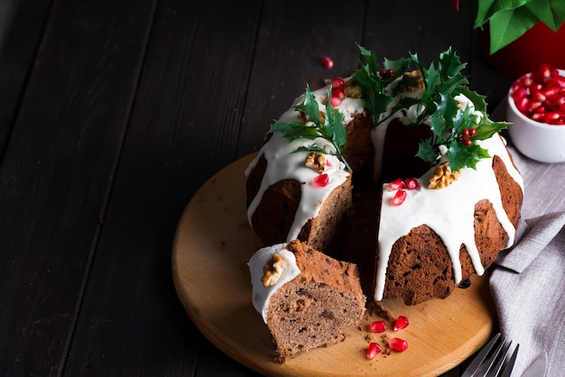 Christmas chocolate cake with white icing and pomegranate kernels on a wooden dark  with red lantern and poinsettia Premium Photo