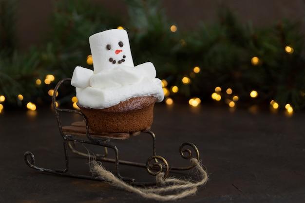 Christmas chocolate cupcakes with snowman decor. on dark background. Premium Photo