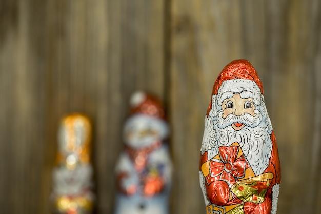 Figure di cioccolato di natale in un involucro su legno Foto Gratuite