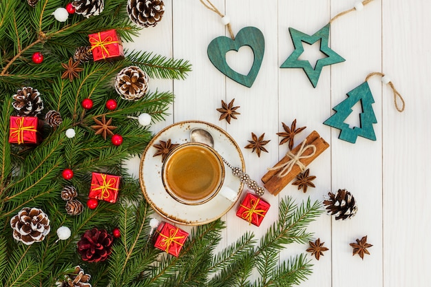 クリスマスコーヒー。青いクリスマス装飾が施された白い木製テーブルの上のコーヒーカップ。上面図 Premium写真