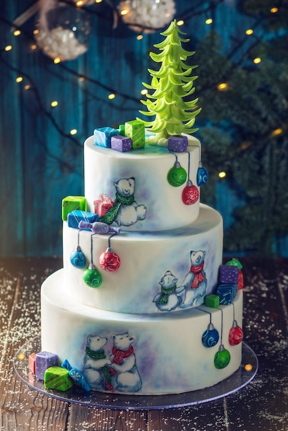 Christmas colorful three-tiered cake decorated with drawings teddy bears, gift boxes and a green tree top Premium Photo