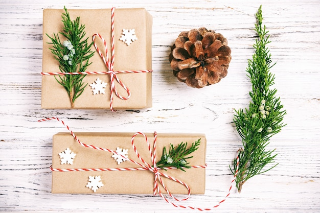 Christmas composition. christmas gift with pine cones and fir branches on wooden. Premium Photo