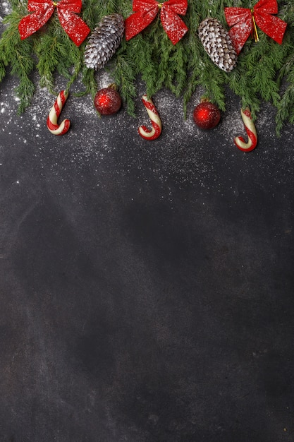 Christmas composition of coniferous branches, decorations and sweets on dark background. flat lay. top view nature new year concept. copy space. Premium Photo