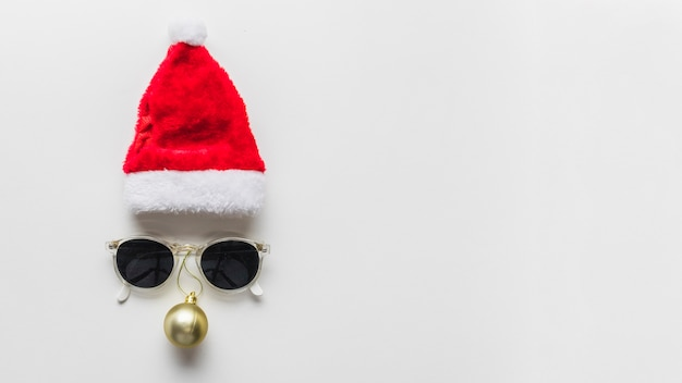 Christmas composition of face from hat and sunglasses Free Photo