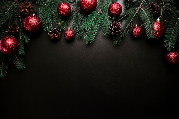 Christmas composition of fir tree branches with baubles and cones Free Photo