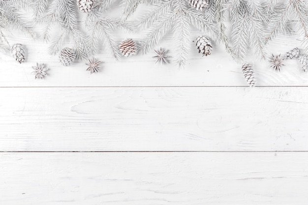 Christmas composition. frame made of fir branches on white wooden background Premium Photo