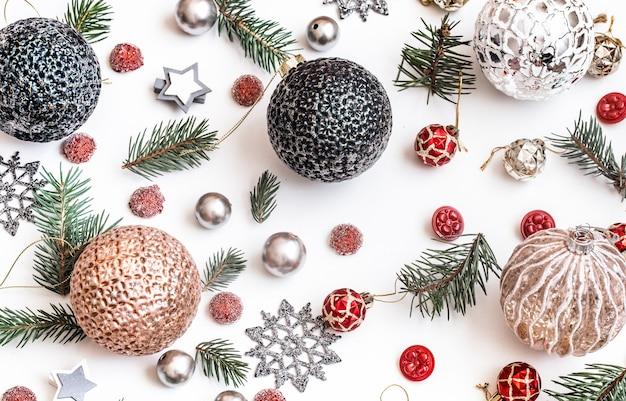 クリスマス作曲。贈り物、モミの木の枝、白い壁に赤い装飾。冬、新年のコンセプト。フラットレイ、アイソメビュー 無料写真