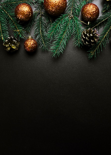 Christmas composition of green fir tree branches with gold baubles Free Photo