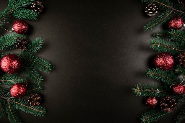 Christmas composition of green fir tree branches with red baubles Free Photo
