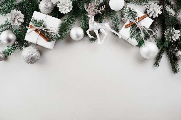 Christmas composition of green fir tree branches with silver baubles Free Photo