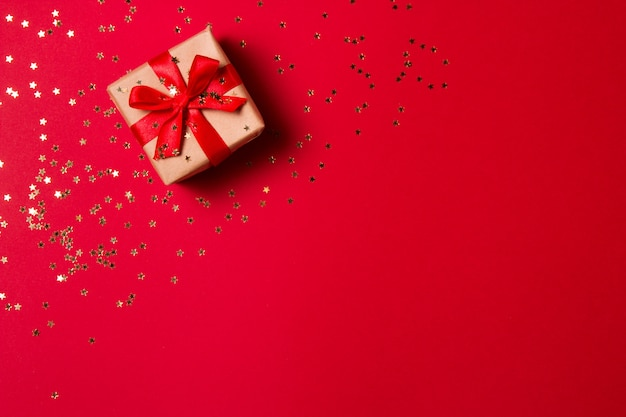 Christmas composition greeting card. gift from craft paper on a red with a gold star confetti Premium Photo