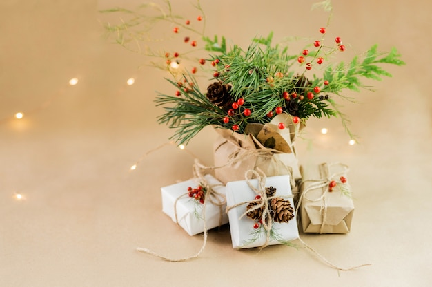Christmas composition of natural materials. christmas gift wrapped, knitted blanket, pine cones, fir branches. flat lay, top view Premium Photo