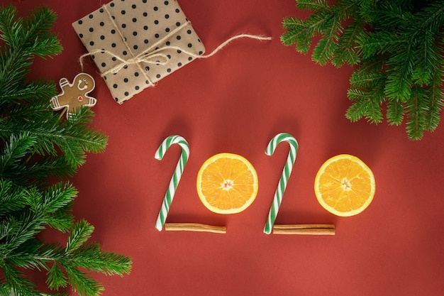 Christmas composition. number 2020 made of candy and half oranges. branches of spruce. christmas presents, winter, new year concept. flat lay, top view, copy space Premium Photo