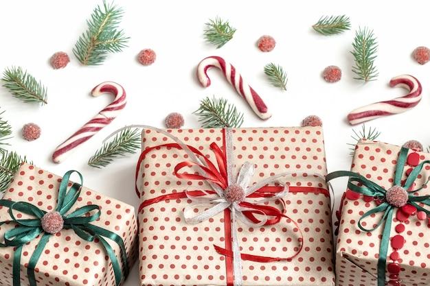 공예 종이에 싸서 새틴 리본으로 장식 된 다양한 선물 상자의 크리스마스 구성. 평면도, 평면 누워. 흰 벽. 무료 사진