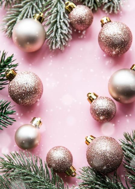 クリスマスの作文。パステルピンクの背景にピンクの装飾。クリスマス、冬、新年のコンセプト。フラットレイ、上面図、コピースペース Premium写真