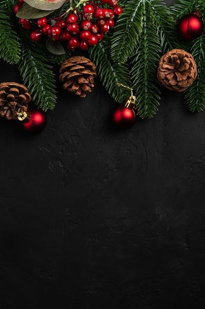 Новогодняя композиция. красный орнамент, украшения сосновых шишек и хвои на темной поверхности. копирование пространства с видом сверху Premium Фотографии