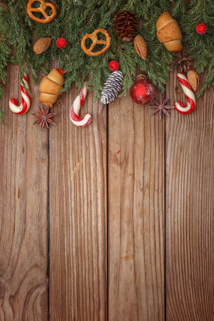 Christmas composition of tree branches, candies and decorations on wooden background. top view. copy space. Premium Photo