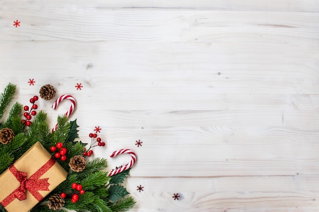 Christmas composition with fir branches, candy, gifts, pine cones and stars on light wood Premium Photo