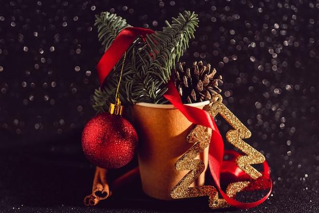Новогодняя композиция с еловыми шишками в бумажной кофейной чашке, элементы праздничного декора Бесплатные Фотографии