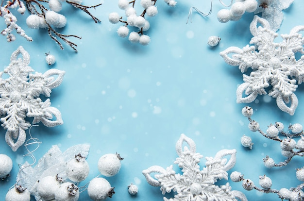 パステルブルーの表面に白い装飾で作られたフレームとクリスマスの構成 Premium写真