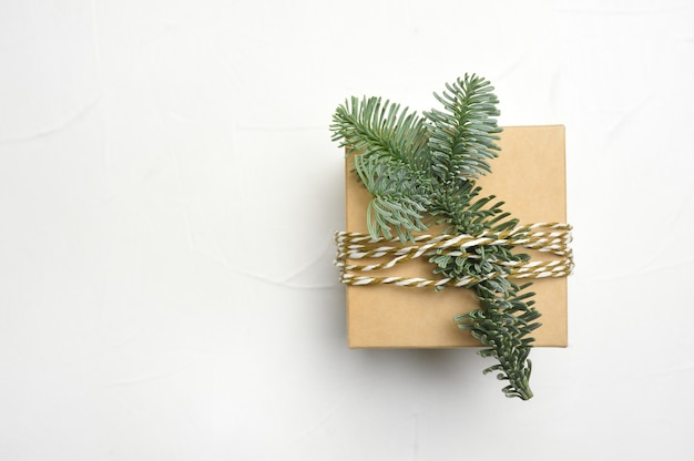 Christmas composition with green fir branches and kraft gift box on white wooden background with copyspace. Premium Photo