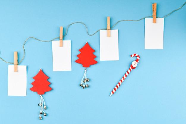 Новогодняя композиция с различными предметами для письма. студия выстрелил над рождественским пространством. макет с пустыми листьями. место для письма. вид сверху. на синем пространстве. Premium Фотографии
