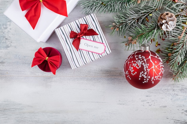 Christmas composition on a wooden  covered in white snow. christmas gift boxes with red bows, snowy fir branches,  holiday decoration with red ball. Premium Photo