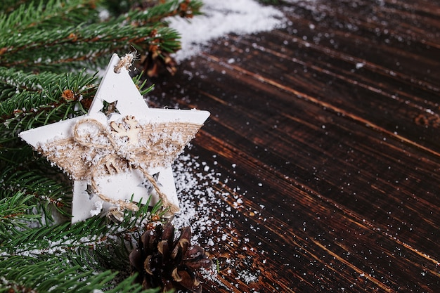 Christmas concept background, handmade star decoration and green christmas trees on a wooden table, dashed by white snow Premium Photo