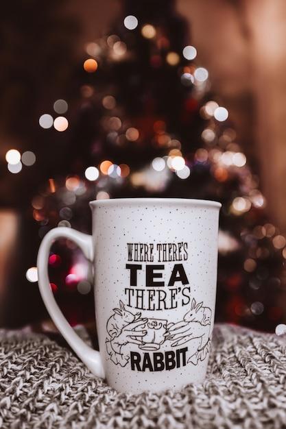 크리스마스 컨셉, Bokeh 흐린 배경 니트 아늑한 소재에 서있는 컵. 프리미엄 사진