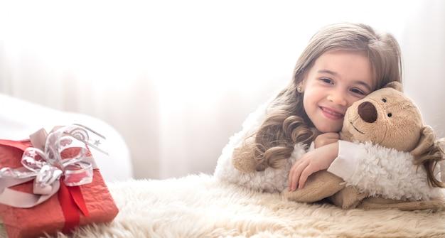 クリスマスコンセプトクマのおもちゃを抱いて少女 Premium写真