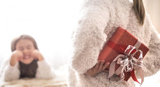 Рождественская концепция, мама дарит подарок маленькой милой дочери Premium Фотографии