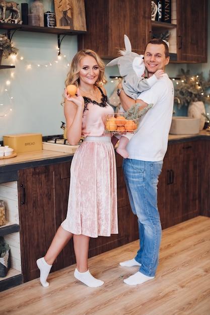 Foto di concetto di natale di gioiosa piccola famiglia di marito, moglie e bambino in posa in cucina ben attrezzata. concetto di vacanza Foto Gratuite