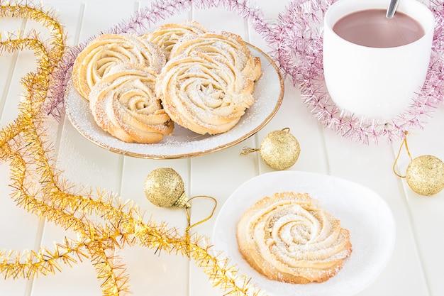 クリスマスのコンセプトです。アイシングとカップホットチョコレートで丸いショートブレッドクッキーバラが形成されます。ビンテージホワイトプレート。多色見掛け倒し。木製の白い背景。 Premium写真