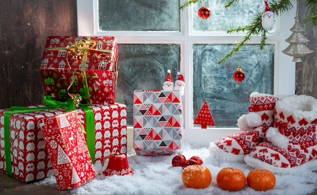 Christmas concept with slippers, oranges and gifts Premium Photo