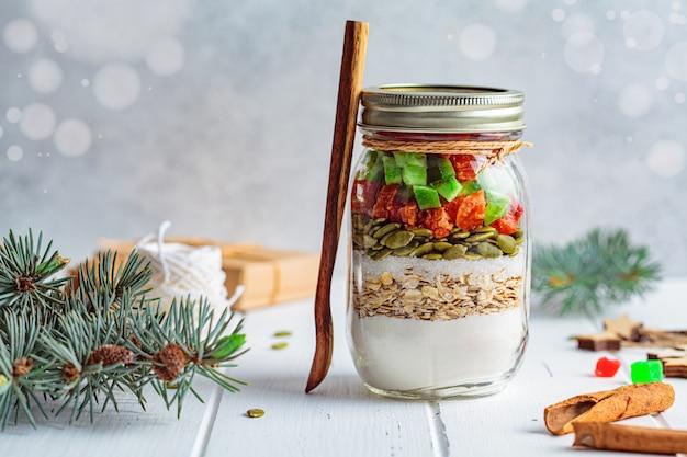 크리스마스 쿠키 믹스 항아리. 항아리, 흰색 배경에서 크리스마스 쿠키 요리를위한 건조 재료. 크리스마스 음식 개념입니다. 프리미엄 사진