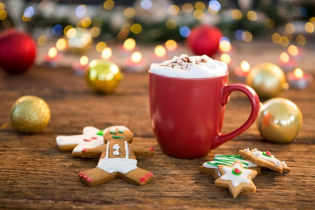 Christmas cookies next to a red cup Free Photo