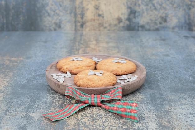 リボンで飾られた木の板に種が付いたクリスマスクッキー。高品質の写真 無料写真