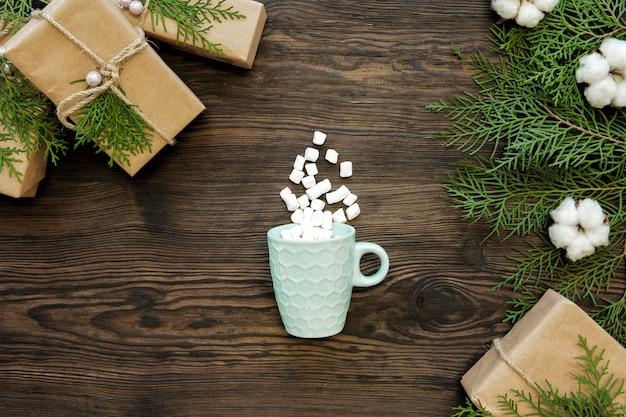 暗い木の板、トップビューでクリスマスカップ、マシュマロ、ギフトボックス Premium写真