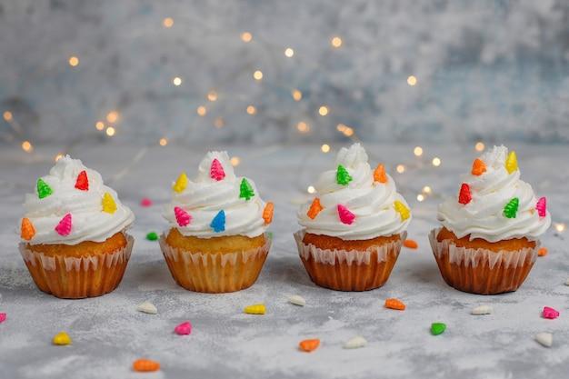 Christmas cupcake with christmas tree shaped sparkler and lights on Free Photo