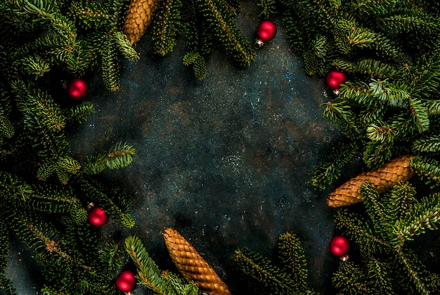 Christmas dark blue background with fir tree branches, pine cones and christmas tree balls copy space above frame Premium Photo