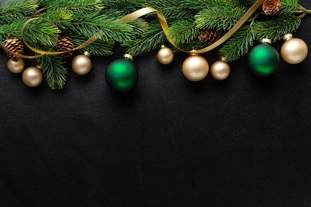 Рождественское деко с елью и шарами на темном фоне. flat lay. рождественское понятие Premium Фотографии