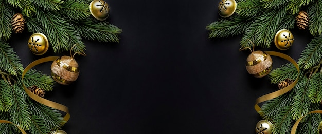 Christmas deco with fir and baubles on dark background. flat lay. christmas concept. horizontal Premium Photo