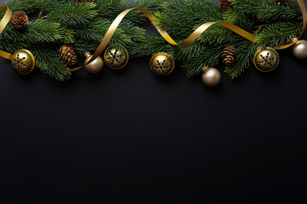 Christmas deco with fir and baubles on dark background. flat lay. christmas concept Premium Photo