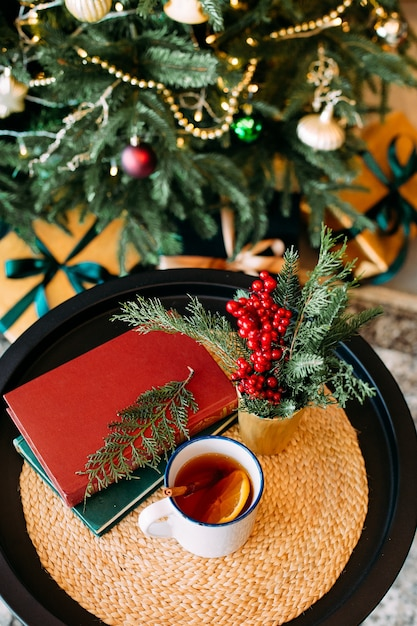 Christmas decor and a cup of tea with bokeh garlands on the christmas tree and green velvet sofa Premium Photo