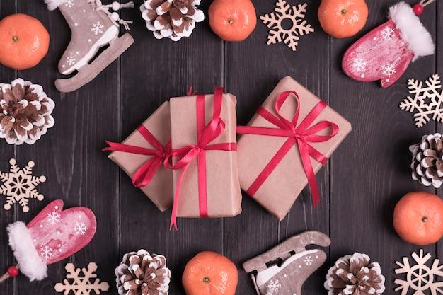 Christmas decor. skates, mittens, snowflakes, tangerines, cones, box on wooden background flat lay Premium Photo