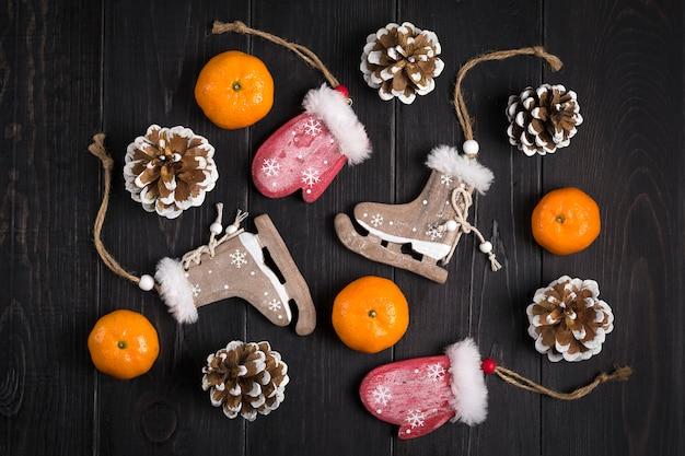 Christmas decor. skates, mittens, snowflakes, tangerines, cones on wooden background flat lay Premium Photo